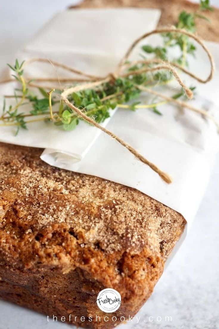 Loaf of sugar and cinnamon topped healthy snickerdoodle zucchini bread wrapped with some string and a sprig of fresh thyme.