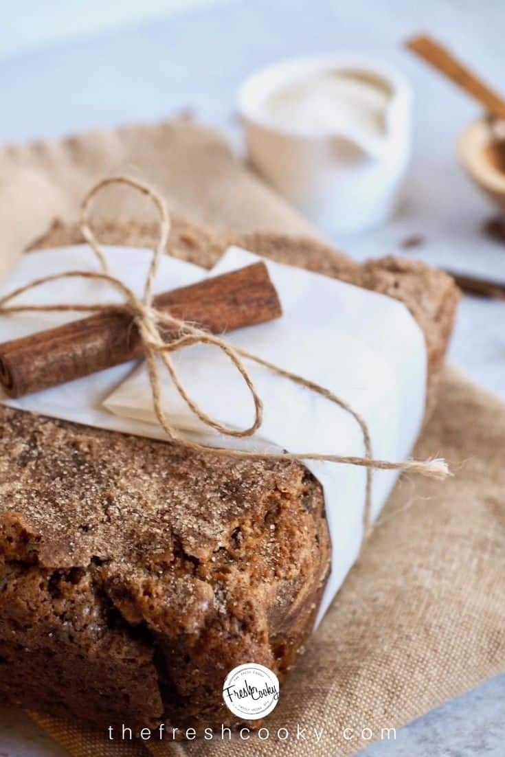 Loaf of Healthy Zucchini Bread wrapped in a strip of parchment paper tied with string and decorated with a cinnamon stick.