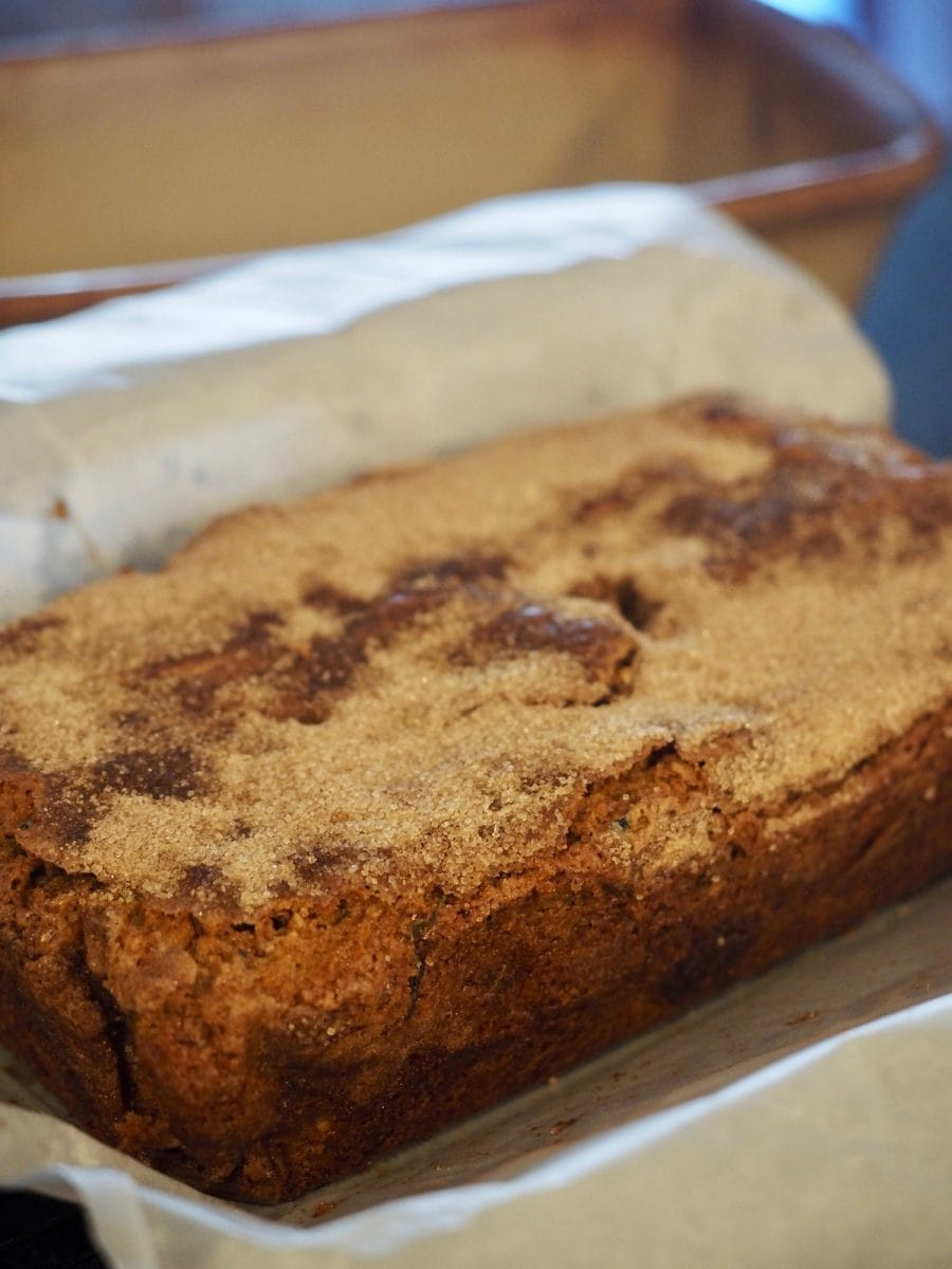 Baked loaf of Snickerdoodle Zucchini Bread in parchment lined loaf pan