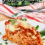 Easy baked spaghetti pie pin with wedge of pasta pie on white plate with fork and knife behind.