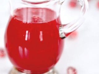 image of small glass pitcher filled with bright red cranberry simple syrup