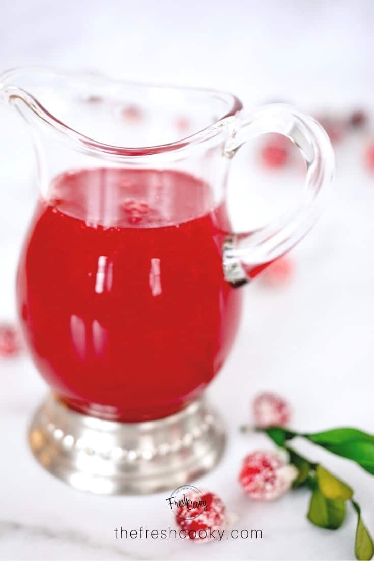 Image of small glass pitcher with bright red liquid simple syrup inside with sugared cranberries and leaves around.