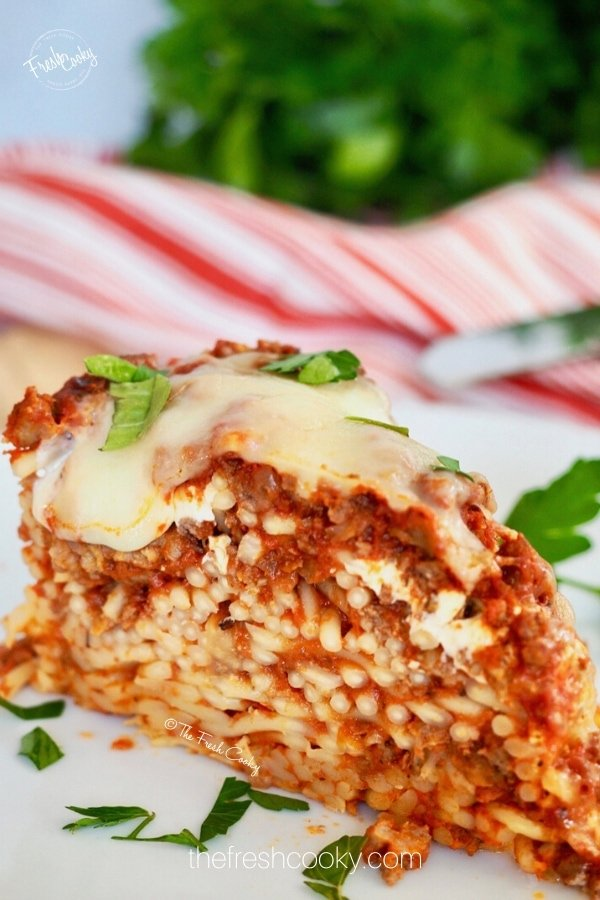 Slice of baked spaghetti pie on a white plate with bits of parsley on top.