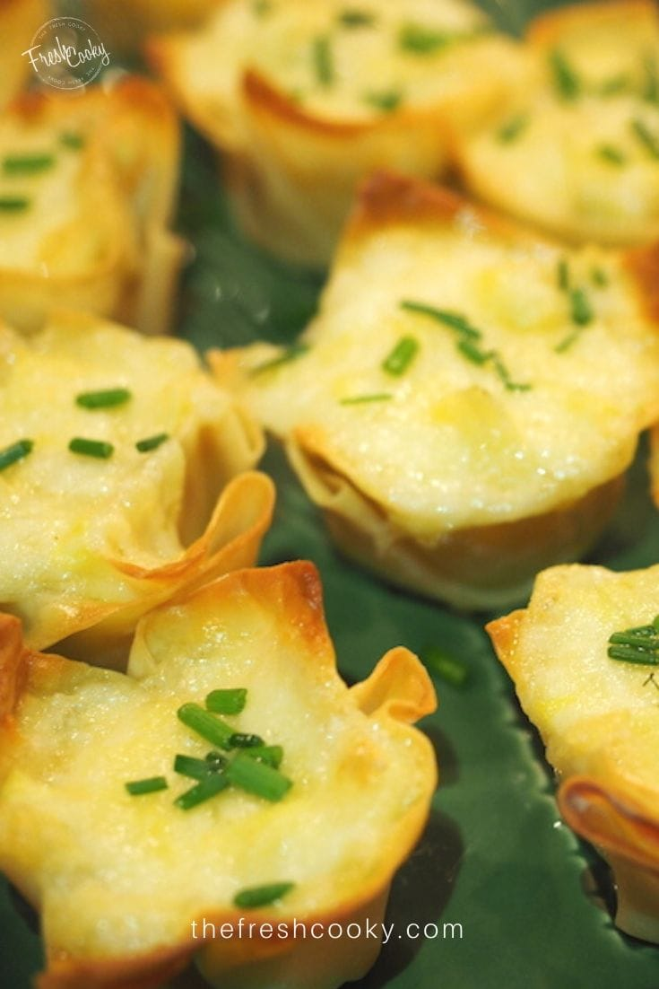 Close up shot of artichoke cheese wontons baked and sitting on a green ceramic platter.