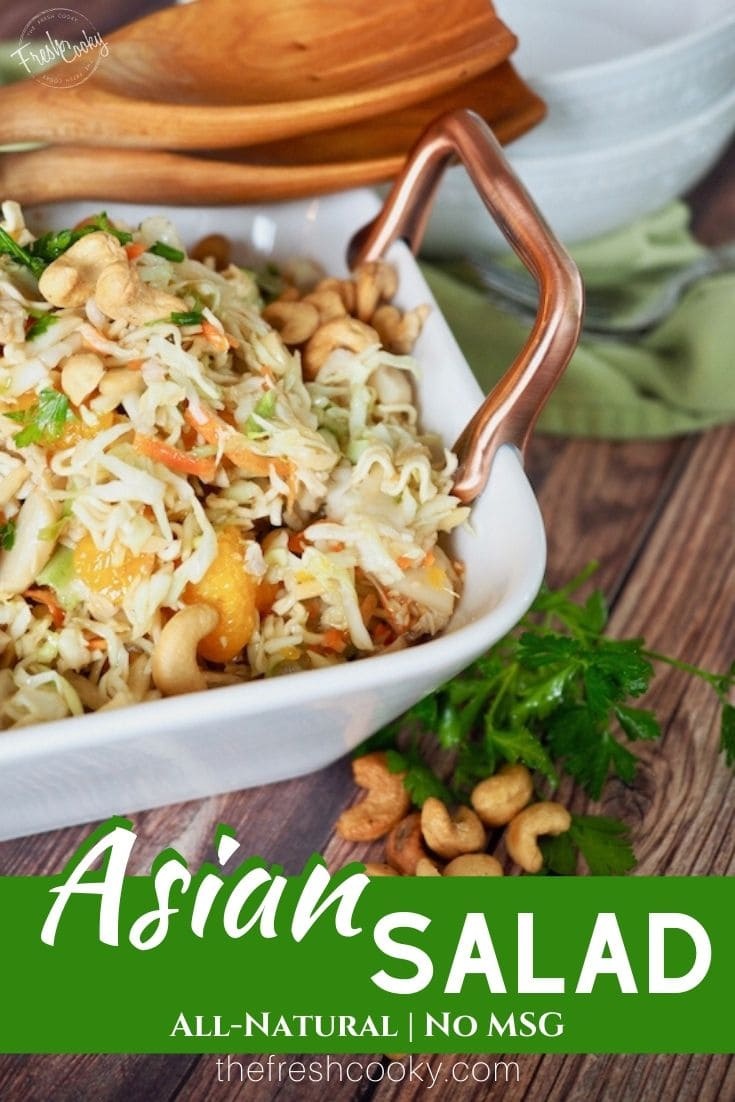 A pinterest image for asian coleslaw in a square bowl with a cabbage salad, mixed with ramen noodles, cashews, cilantro, mandarin oranges with asian dressing with text overlay Asian Salad with all natural | No MSG Recipe via thefreshcooky.com