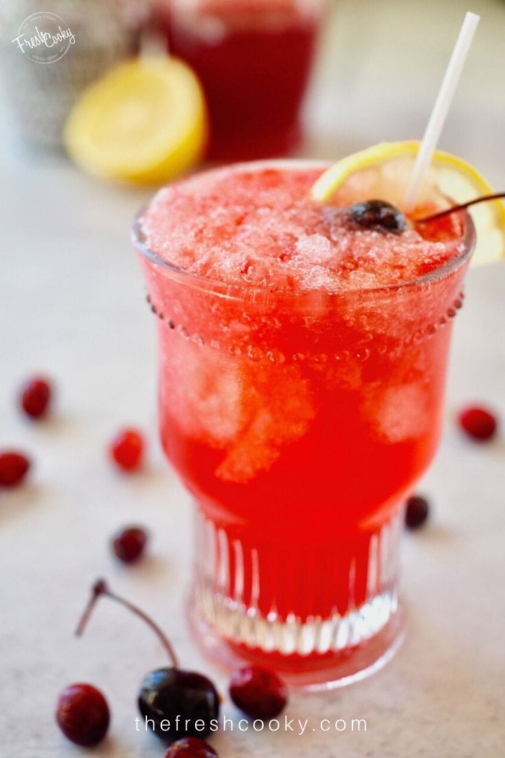 Pretty glass filled with bright red Cranberry Spritzer with cherries.