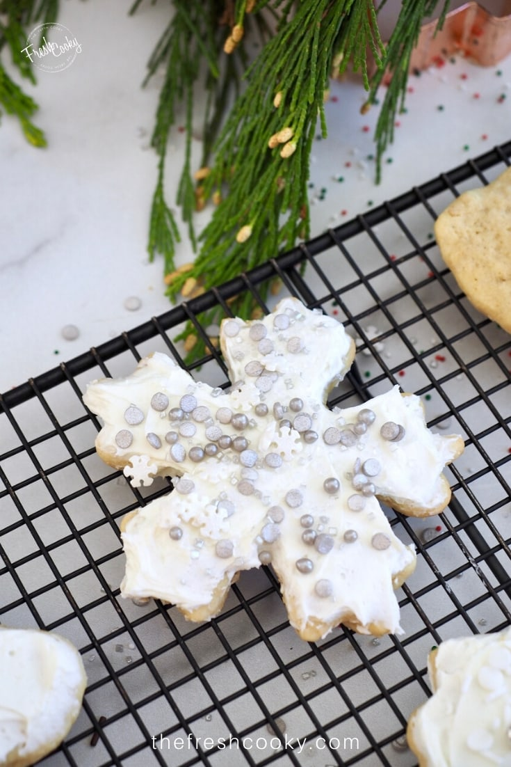 Snowflake cut out cookie, frosted and covered in silver sprinkles.