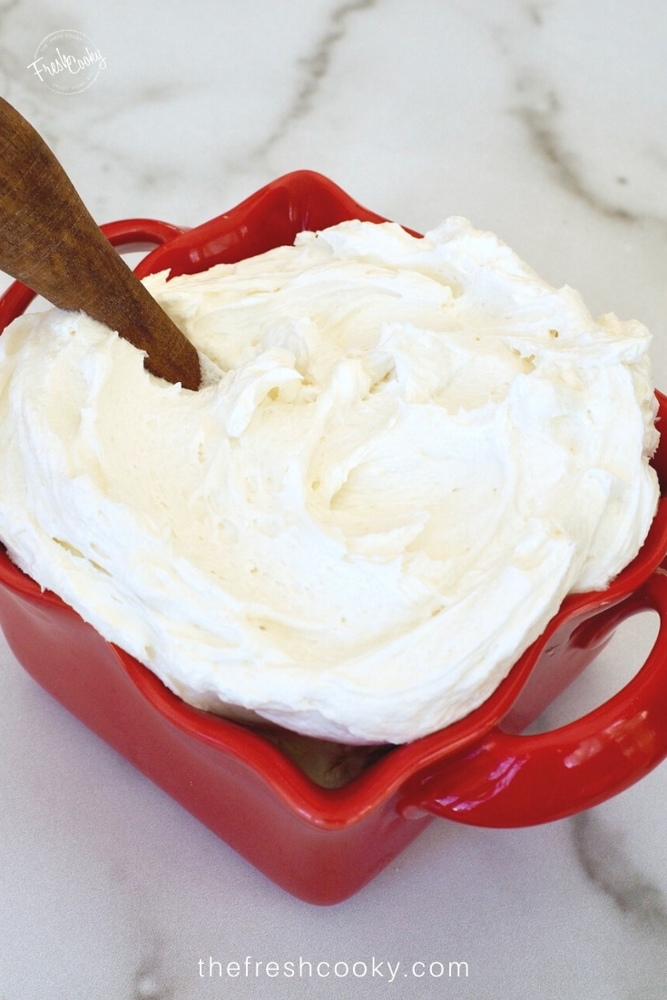Red square bowl filled with vanilla buttercream frosting.