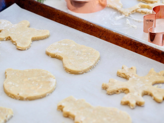 Rolled Oatmeal Sugar Cookies, with cut out cookies on sheet pan and copper cookie cutters in background.