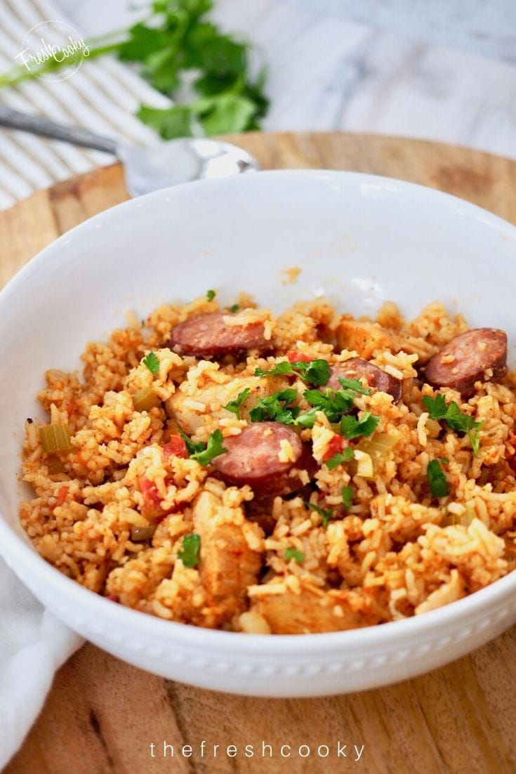 Pinterest image of white bowl of sausage and chicken jambalaya with a spoon in background.