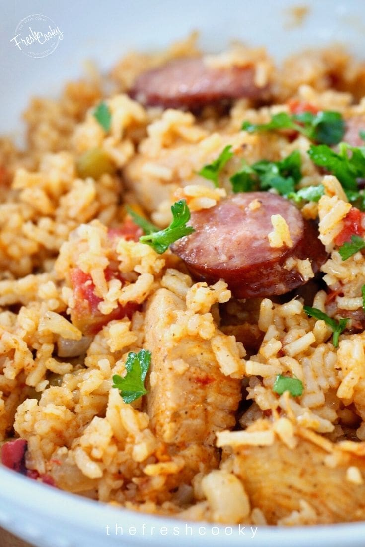 Close up shot of chicken and sausage jambalaya, with sausage slice and dirty looking rice from teh tomatoes, and a sprinkling of bright green parsley!