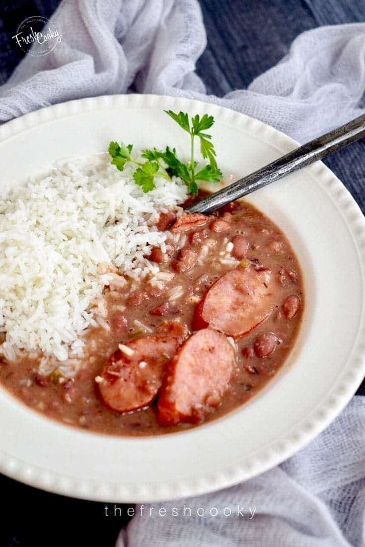 Top down shot of a pretty soup bowl filled with Slow Cooker Red Beans and Rice, with a rustic spoon and a sprig of parsley.