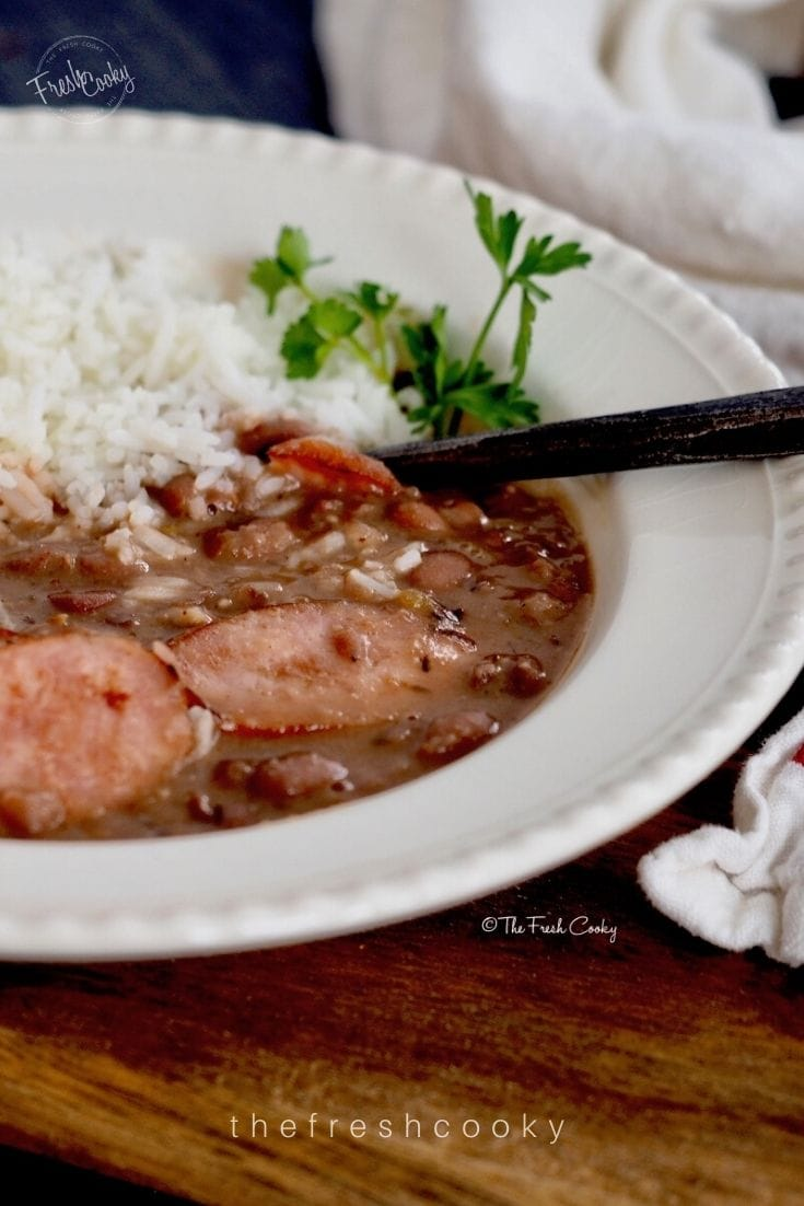 Image of pretty cream bowl filled with white rice and red beans in a sauce for slow cooker red beans and rice.