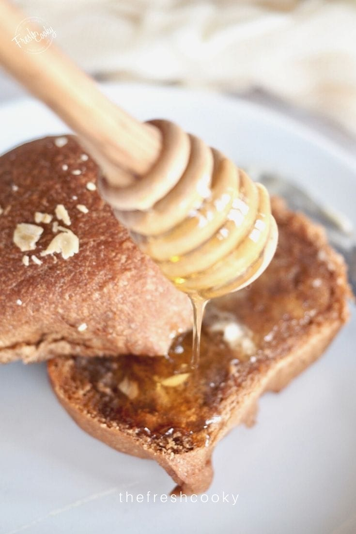 Close up image of a sweet molasses brown bread roll with butter and honey dripping onto the roll