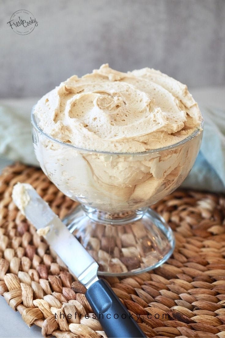 Image of Irish Buttercream for Guinness Chocolate Cake in a pedestal glass bowl on rattan platemat with offset spatula