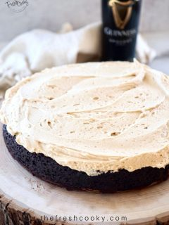 high altitude Chocolate Guinness Cake with Irish Buttercream frosting on a slice of wood with a bottle of Guinness in the background