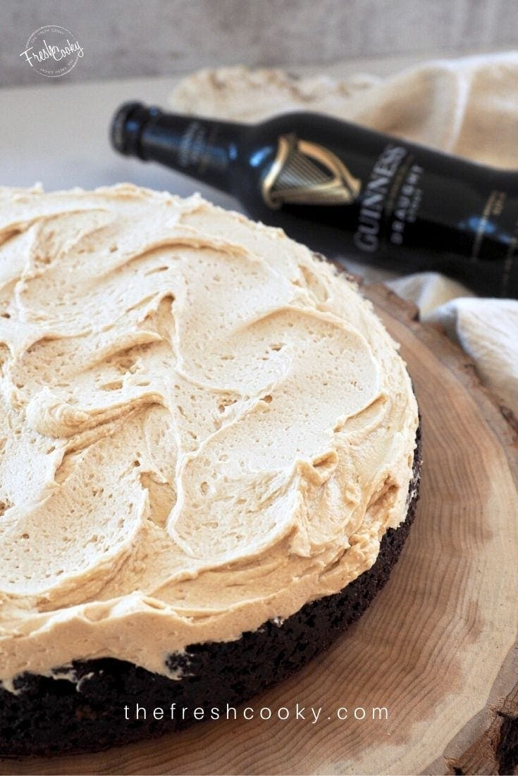 Image of a single layer round Guinness Chocolate Cake topped with light and fluffy Irish Cream Buttercream frosting, sitting on a wooden plate.