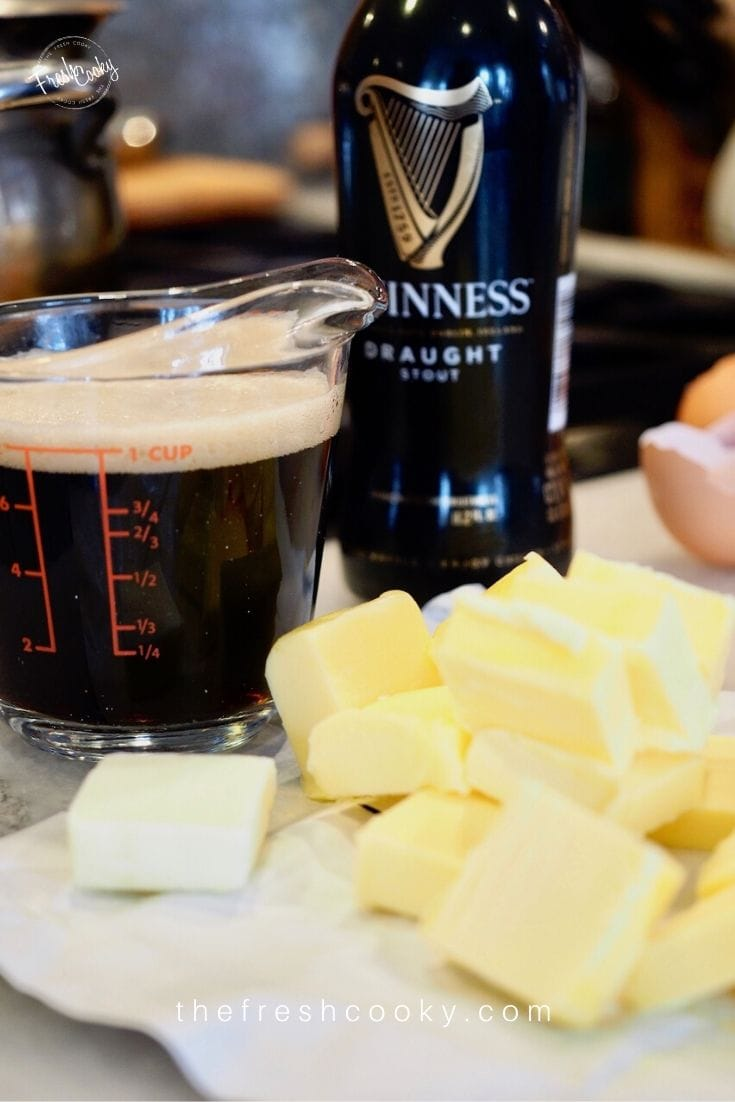 Image of Guinness bottle, guinness poured into measuring cup with head on top, sliced butter and egg shells on a marble board for Guinness Chocolate Cake with Irish Buttercream