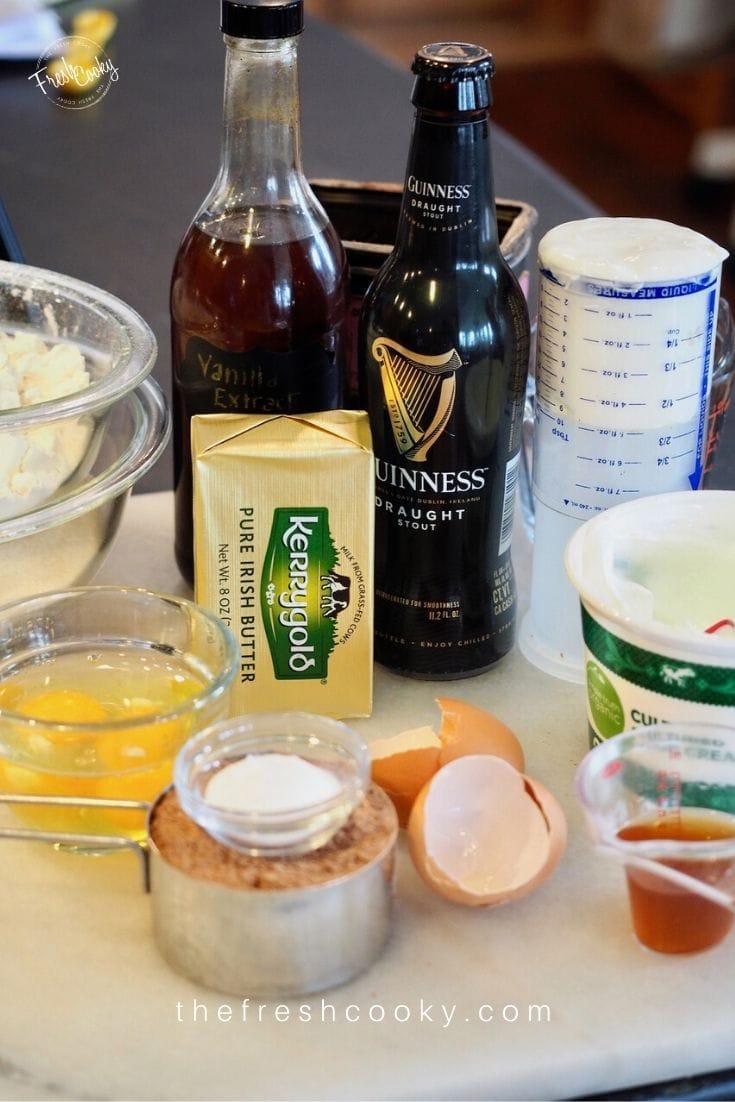 Ingredient shot for Guinness Chocolate Cake with Irish Buttercream L-R Flour, Sugar, Beer, Vanilla, Sour Cream, Irish Butter, Eggs, Brown Sugar, Baking Soda and salt.