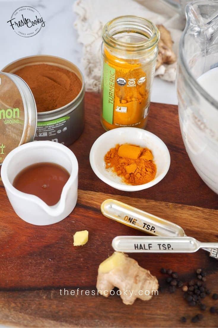 Ingredients for Golden Milk Turmeric Tea on wooden cutting board.