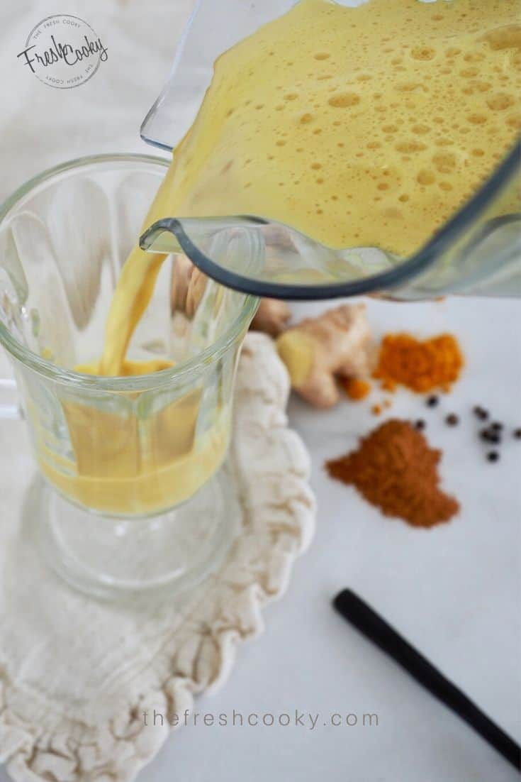 Glass mug with golden milk tea in it with a spoon and spices on the counter.