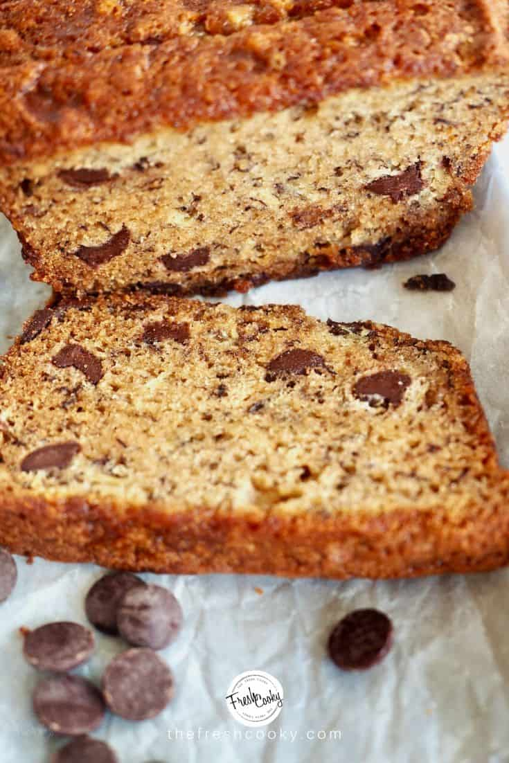 Image of high altitude banana bread sliced with chocolate chips on a parchment lined tray