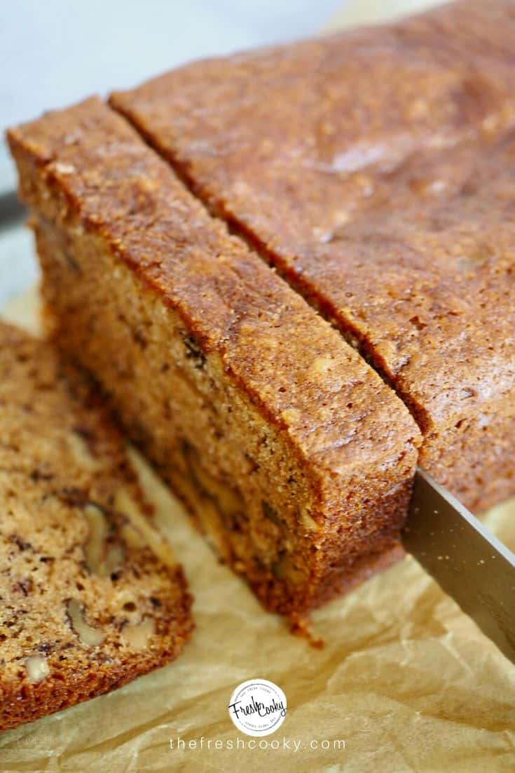 A serrated knife slicing a large slice of high altitude banana nut bread.