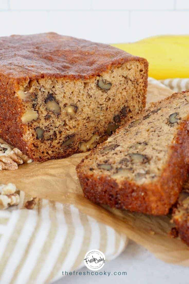 Slices of a loaf of high altitude banana bread with nuts on a natural piece of parchment paper with walnuts strewn about, on top of a tan and white striped tea towel.