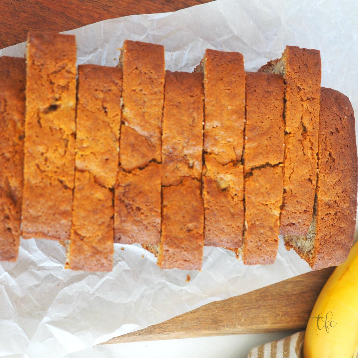 Square image of alternating slices of easy banana bread recipe with banana in corner, rich, golden banana bread.
