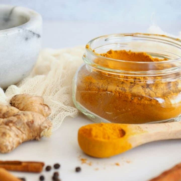 golden milk spice mix with mortar and pestle in background as well as fresh ginger root, black peppercorns and cinnamon sticks, with jar filled with golden milk spice mix