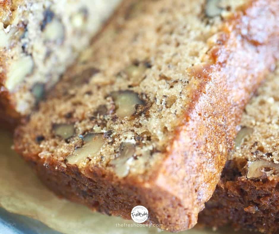 Facebook image of closeup of high altitude banana bread with nuts on parchment lined tray, overlapping each other.