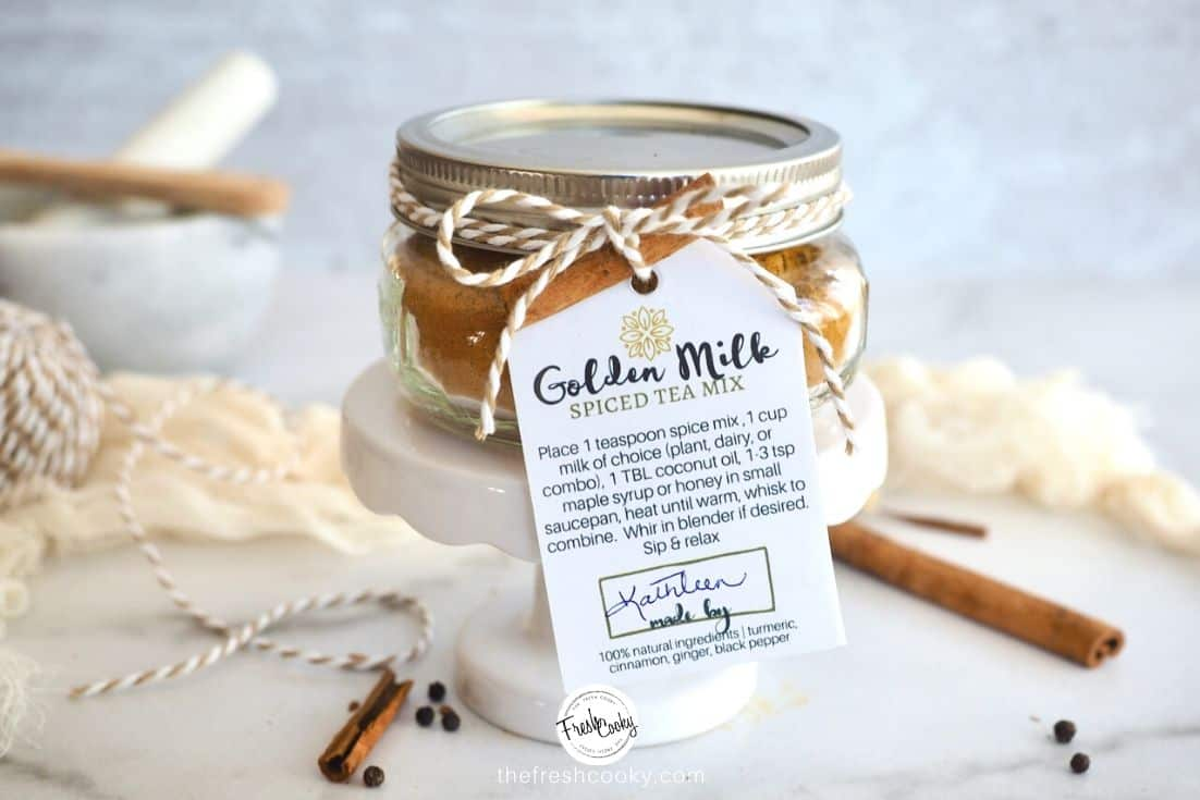 Jar of Golden Milk Spice Mix on a mini pedestal with a gift label tied around it and cinnamon sticks behind.