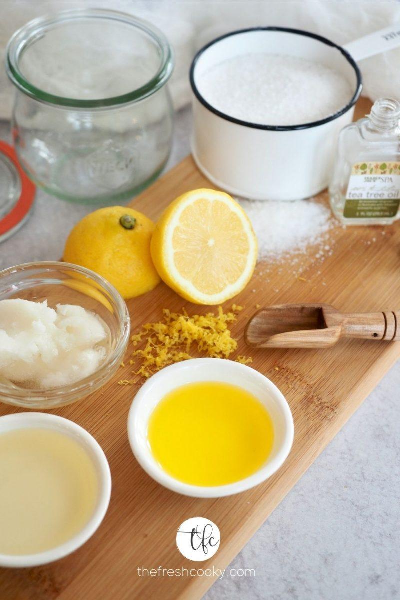 Anitbacterial Handscrub on wooden cutting board ingredients. Kosher Salt, Fresh Lemon, Jojoba Oil, Coconut Oil, Sweet Almond Oil, Esseintial Oils.