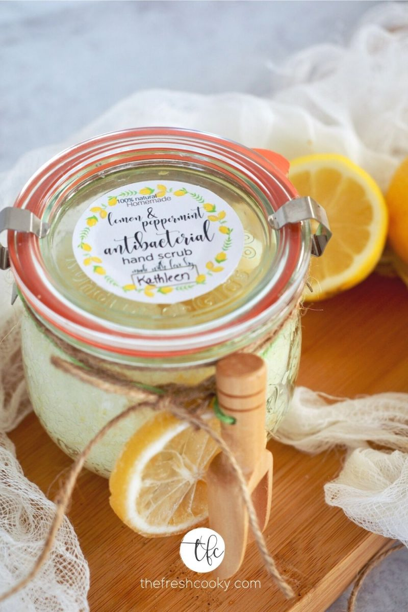 Top down shot of jar of lemon peppermint antibacterial hand scrub with free label, tied with dried lemon and a wooden scoop.