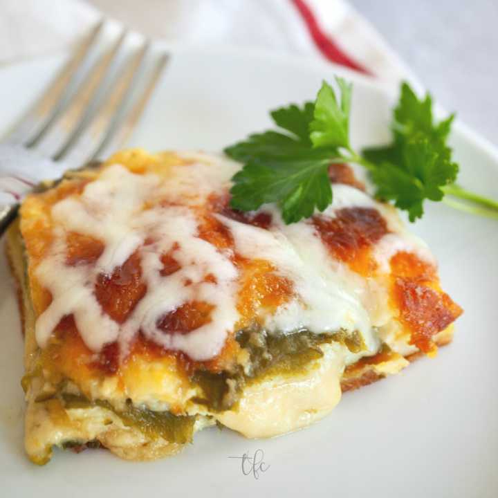 Square of chile relleno casserole on a plate with a fork and cheese oozing from chile.