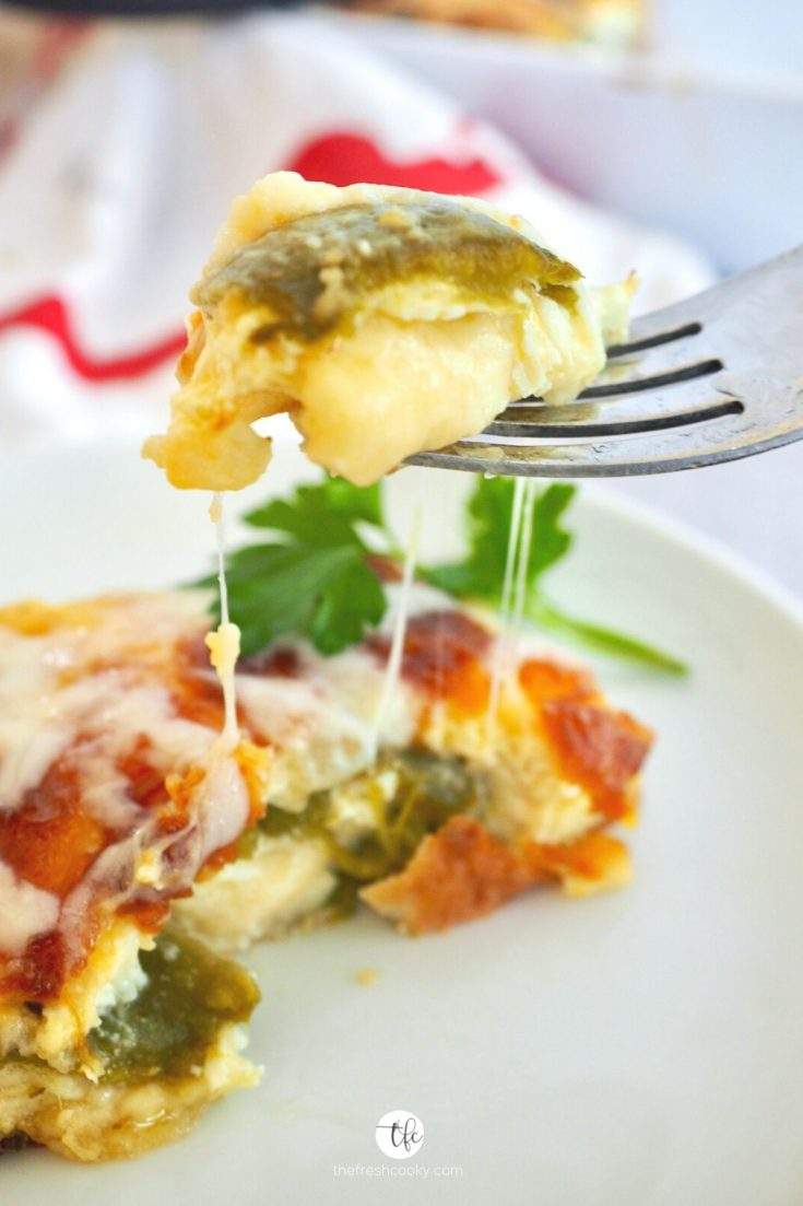 Piece of Chile Relleno Casserole on a white plate with a fork holding up a melting cheesy bite.