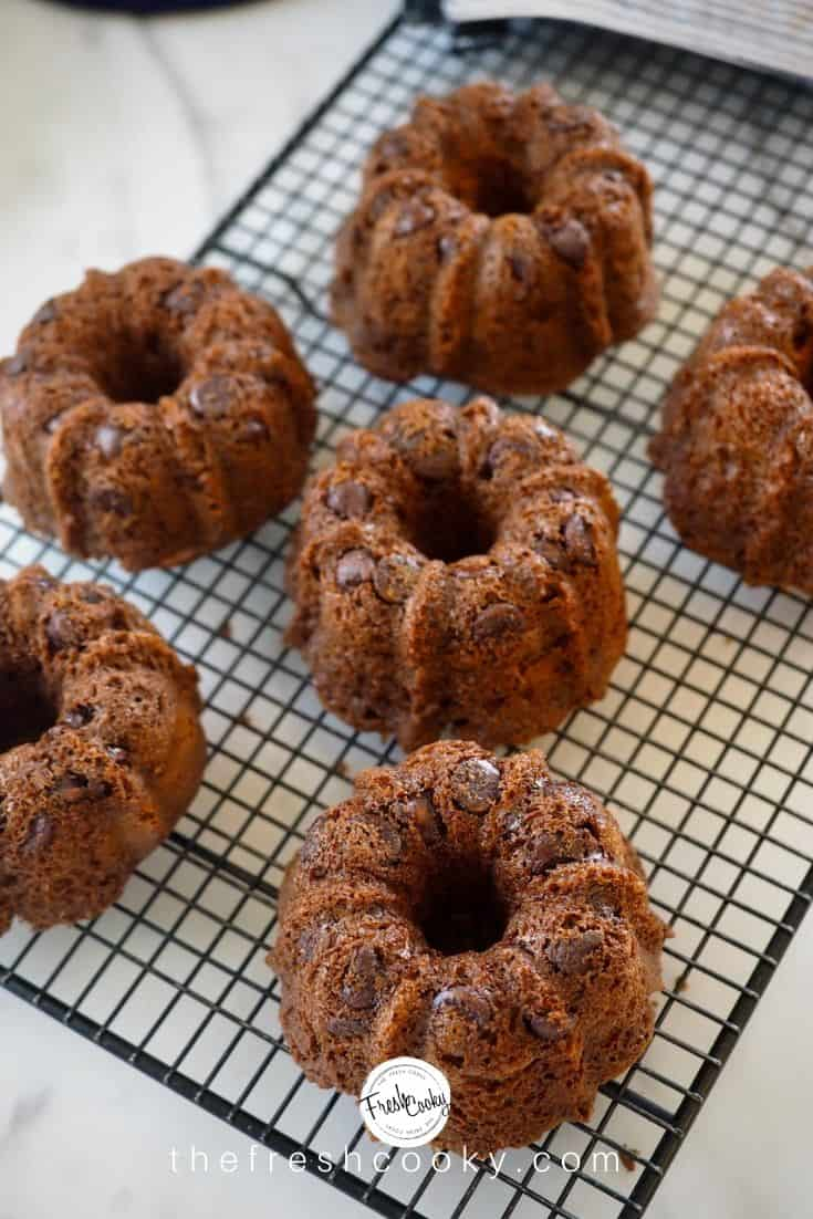 Chocolate Chocolate Chip mini bundt cakes cooling on a wire rack with large chocolate chips shimmering on the surface. | via thefreshcooky.com