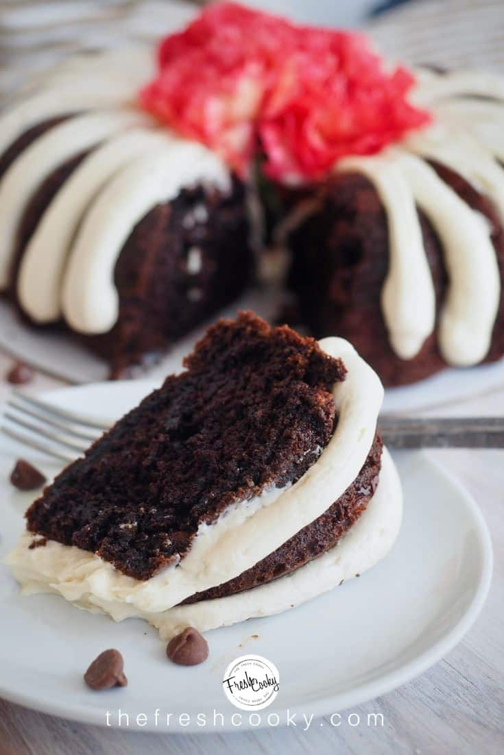 A pin image of a rich, moist slice of chocolate chocolate chip bundt cake on a plate with a rustic fork in the foreground, background has the rest of the cake, with a slice removed. via thefreshcooky.com