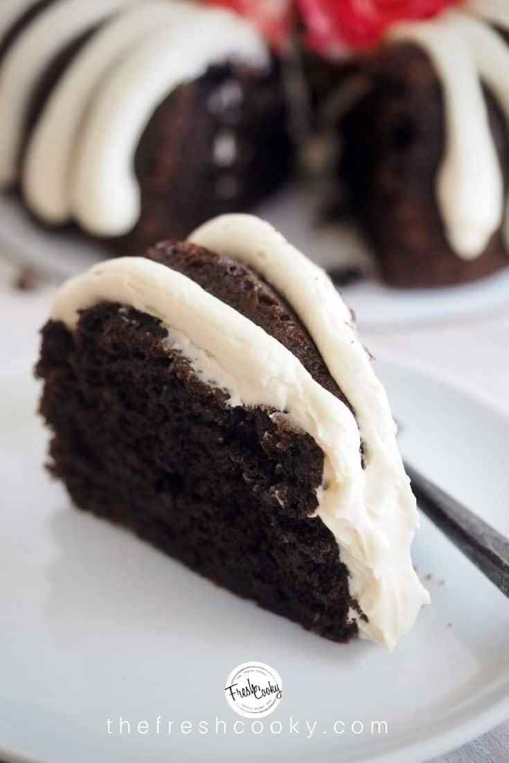 A Pinterest image of a rich, moist slice of chocolate chocolate chip bundt cake on a plate with a rustic fork in the foreground, background has the rest of the cake, with a slice removed. via thefreshcooky.com
