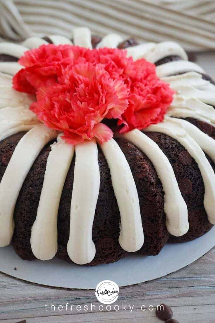 A decorated full size chocolate chocolate chip bundt cake, like Nothing Bundt Cakes with thick fingers of brown sugar cream cheese frosting, topped with coral carnations. via thefreshcooky.com