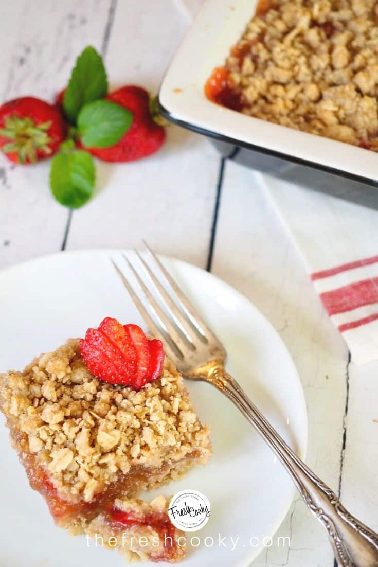 white plate with silver fork and square of rhubarb strawberry crumble bar with sliced strawberry on top and pan of rhubarb crumble in background.