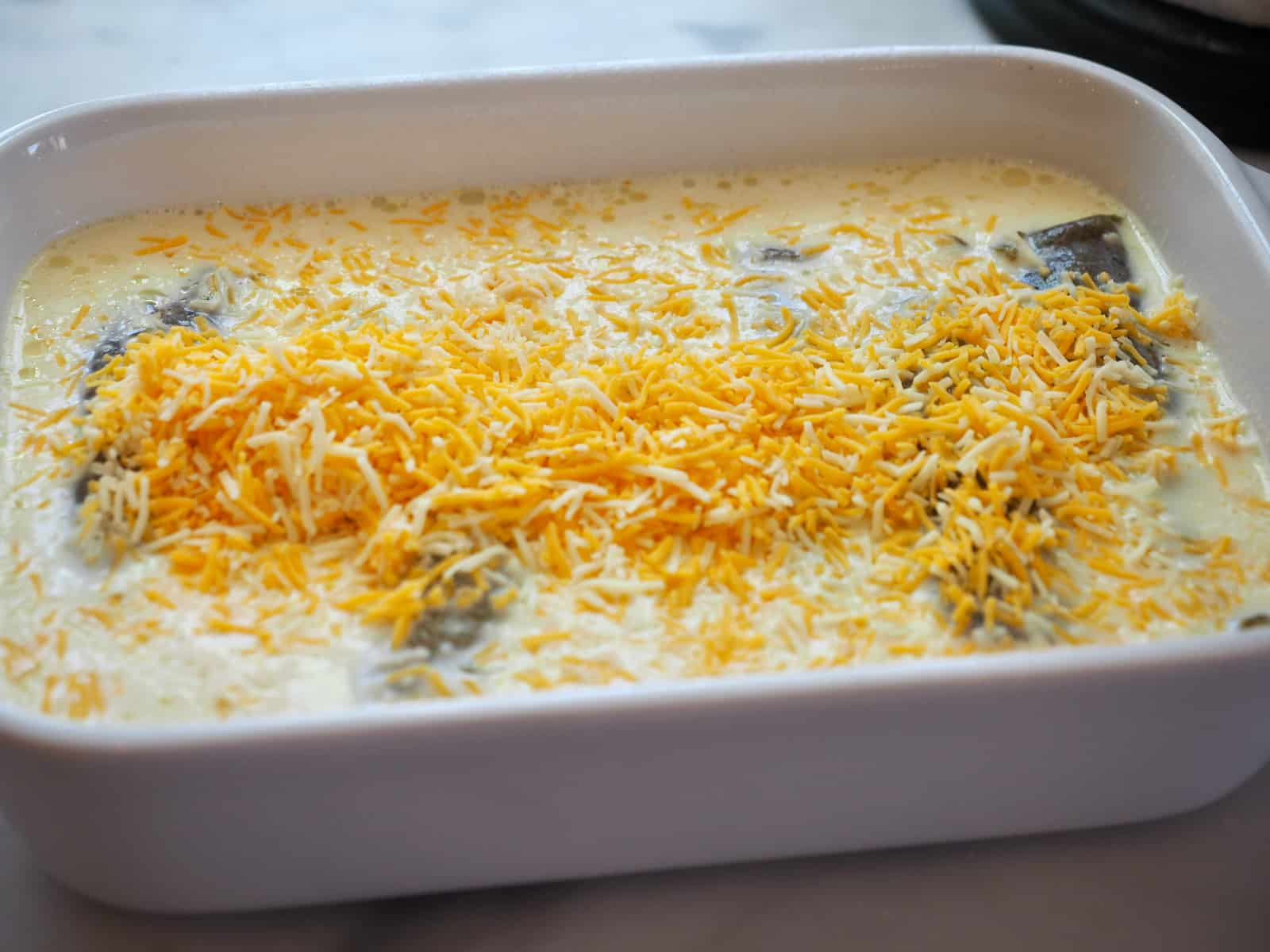 casserole with hatch green chiles stuffed with cheese, with a milk, egg mixture poured on top, sprinkled with more grated cheese. Easy Chile Rellenos | thefreshcooky