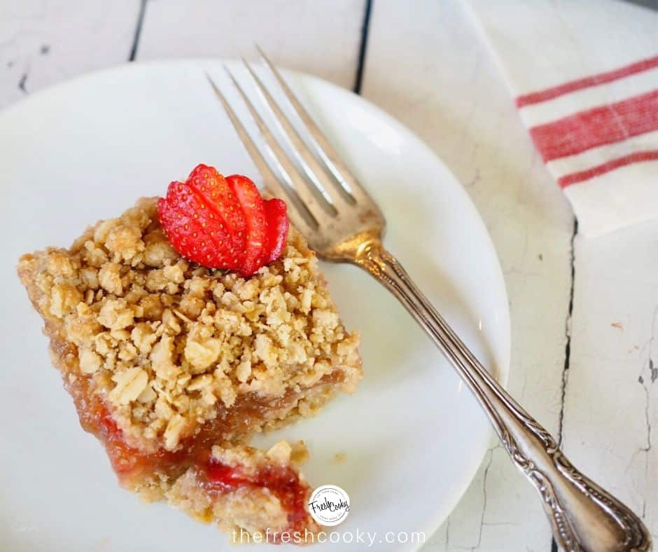 facebook image for gluten free strawberry rhubarb crisp with square on plate with antique silver fork.