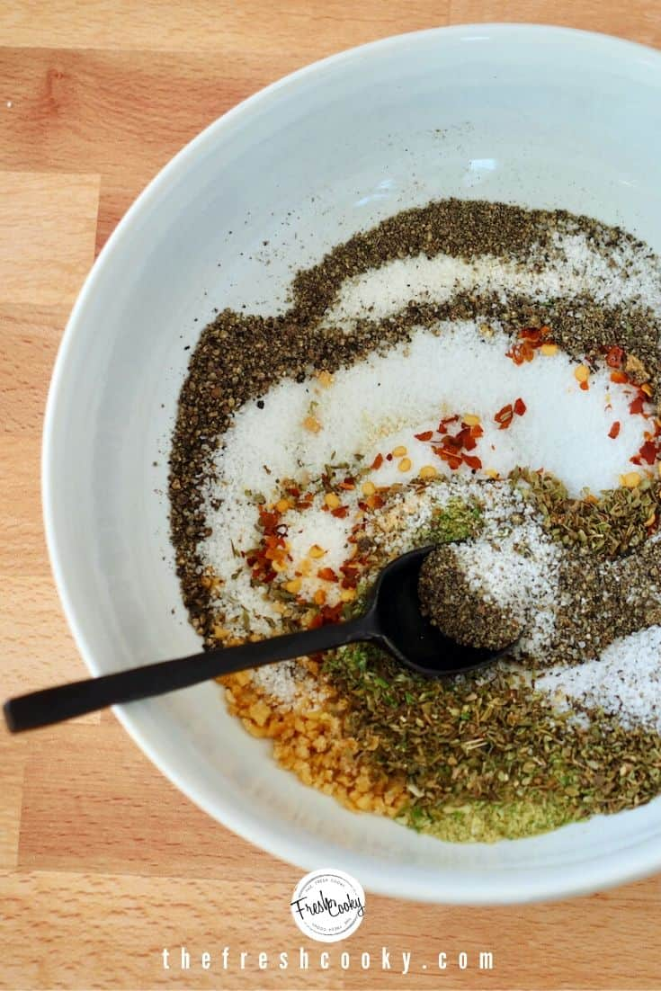 white bowl of swirled/stirred spices for dry rub with black spoon.