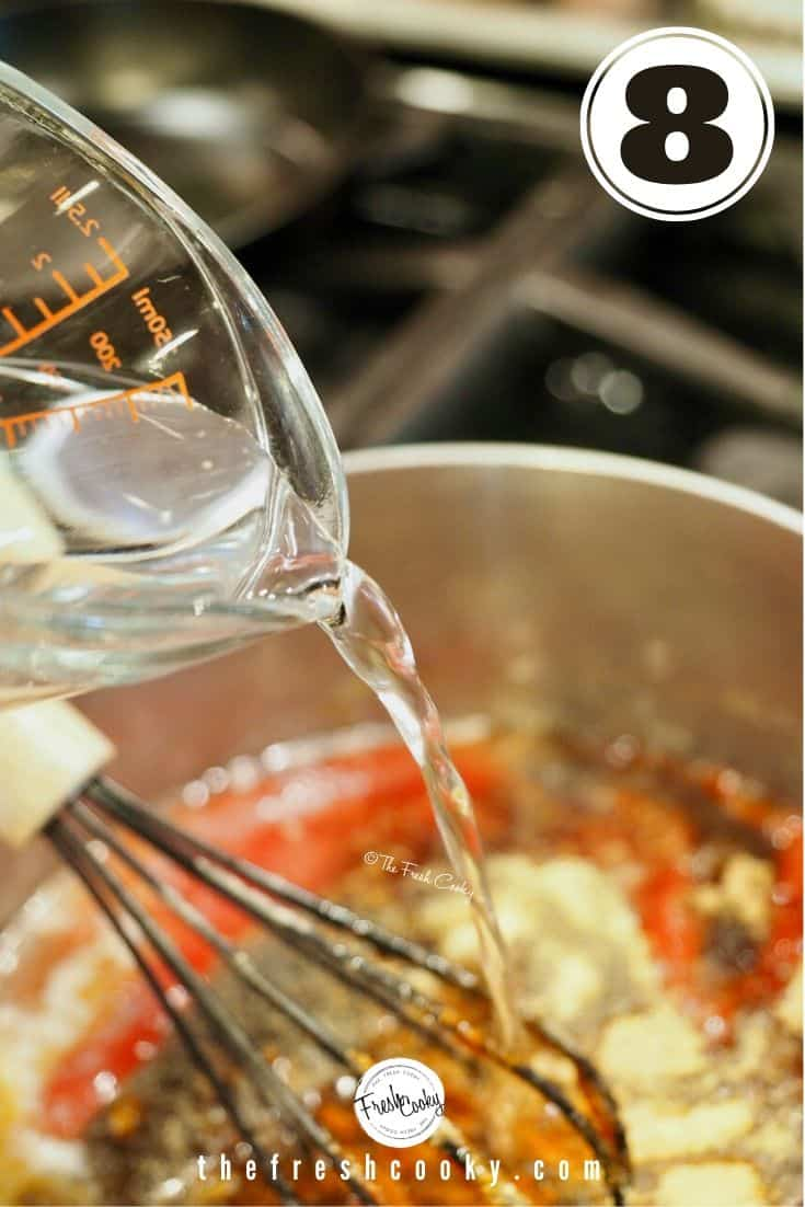 Pouring water into barbecue sauce mixture from glass measuring cup with black whisk in background