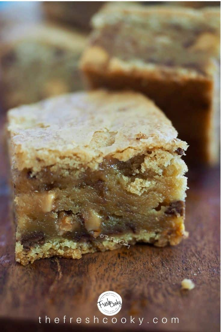 Close-up image of heath bar and butterscotch blondie square sitting on dark cutting board