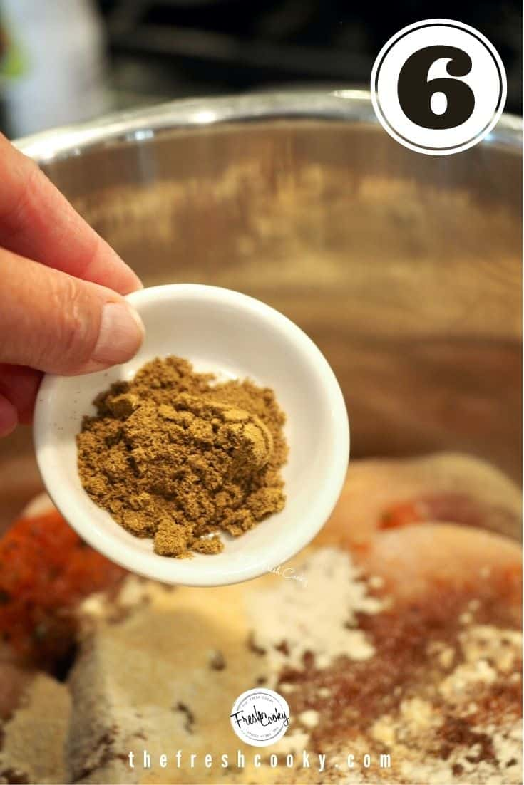 A small white bowl with cumin powder reading to pour in instant pot with chicken