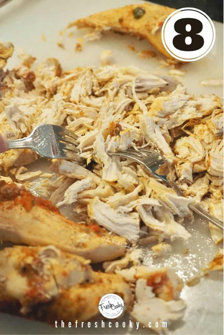 two forks with shredded chicken on a cutting board