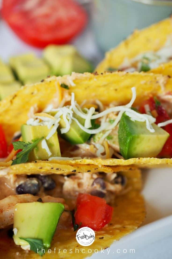 Close up of tacos with crack chicken, fresh avocado, tomatoes and shredded cheese