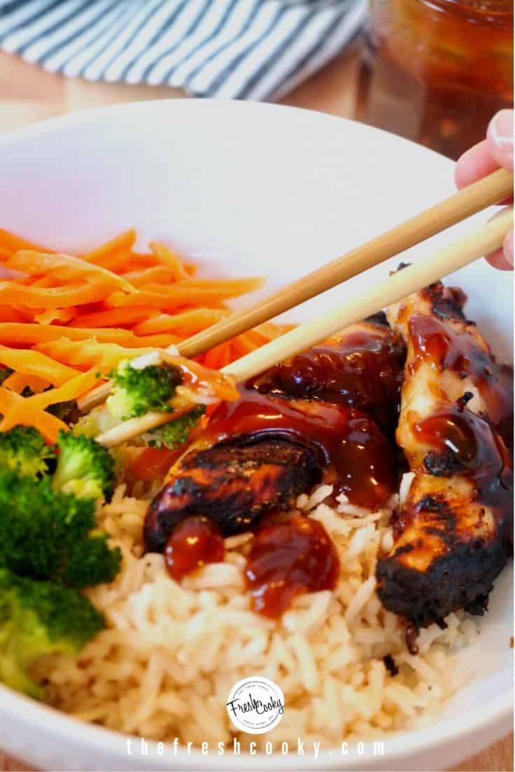 Chopsticks picking up broccoli and teriyaki chicken from large white bowl with brown rice, grilled chicken, shredded carrots, steamed broccoli drizzled with teriyaki sauce.